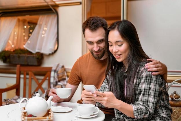 Couple à l'aide de leur téléphone mobile