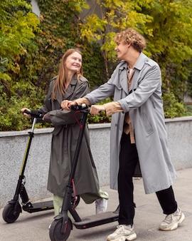 Couple à l'aide d'un scooter électrique à l'extérieur