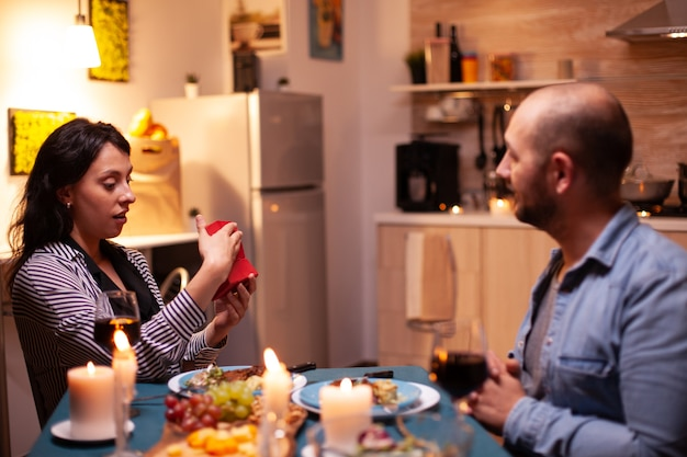 Couple à l'aide de tablet pc avec modèle vert pendant le dîner de fête. mari et femme regardant l'affichage de la clé chroma du modèle d'écran vert assis à la table dans la cuisine.