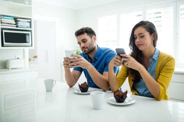 Couple à l'aide de téléphone portable dans la cuisine à la maison