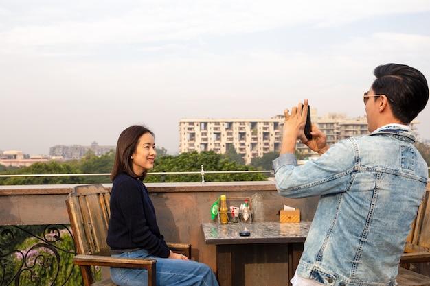 Couple à l'aide de téléphone portable, prenant des photos de l'autre au café en plein air.