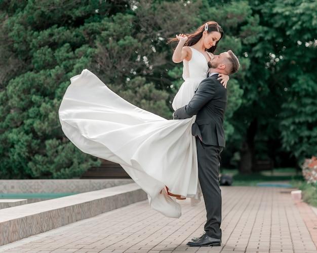 Couple aimant de jeunes mariés debout dans le parc de la ville. vacances et événements