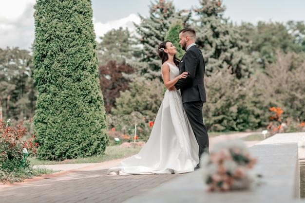 Couple aimant de jeunes mariés debout dans le parc de la ville