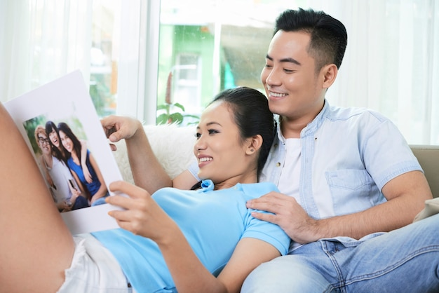 Couple aimant à la recherche d'album photo sur le canapé