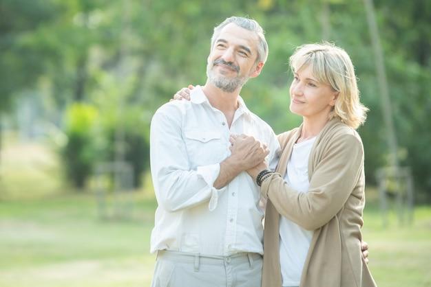Couple aîné, amoureux, tenant mains, dans parc public