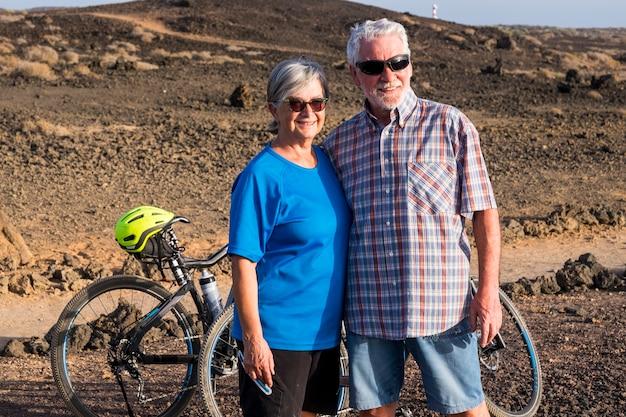 Couple d'aînés mariés regardant quelque chose à la montagne rocheuse avec leurs deux vélos . mode de vie actif homme et femme mature