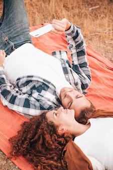Couple allongé sur une couverture prenant un selfie