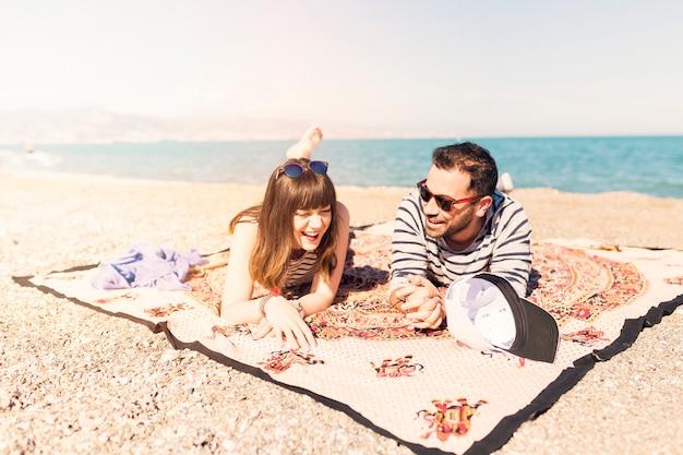 Couple allongé sur une couverture près du rivage
