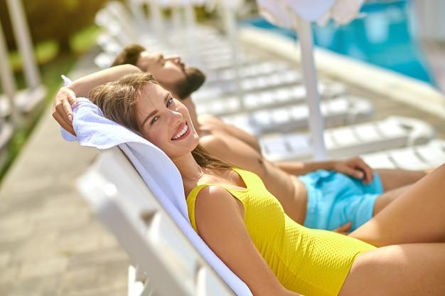 Un couple allongé sur une plage et se sentant détendu