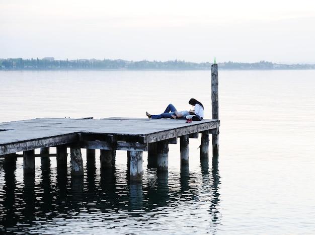 Couple allongé près du quai en bois sur un beau lac