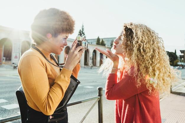 Couple d'amis lesbiennes amoureux et heureux se promenant dans les rues de la ville au coucher du soleil