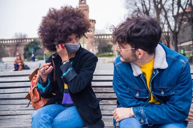 Couple d'amis multiethniques portant un masque médical ayant une conversation