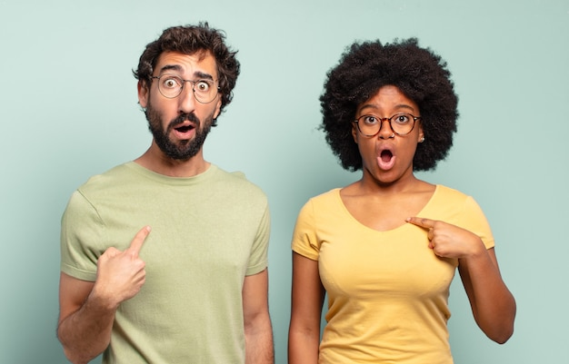 Couple d'amis multiraciaux à la recherche de choc et surpris avec la bouche grande ouverte, pointant vers soi