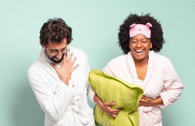 Couple d'amis multiraciaux riant à haute voix à une blague hilarante, se sentant heureux et joyeux, s'amusant. pyjama et concept de maison