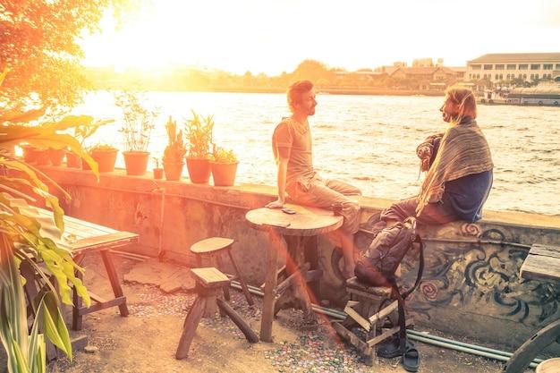 Couple d'amis parlant au coucher du soleil