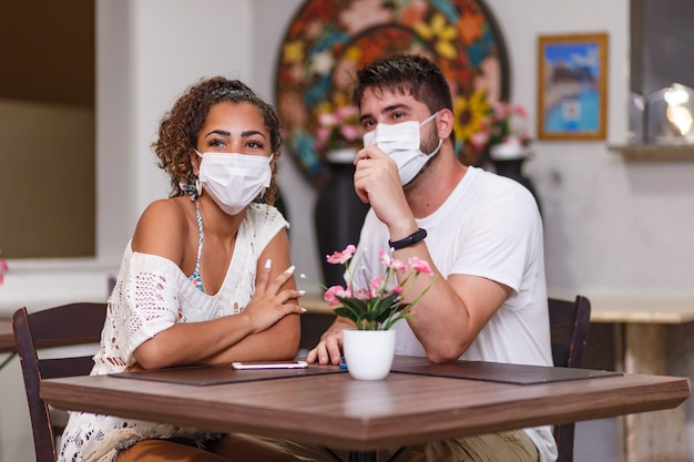 Couple d'amis parlant en toute sécurité assis sur un restaurant en plein air portant un masque de sécurité contre la pandémie de coronavirus covid-19. nouveau concept de vie normale