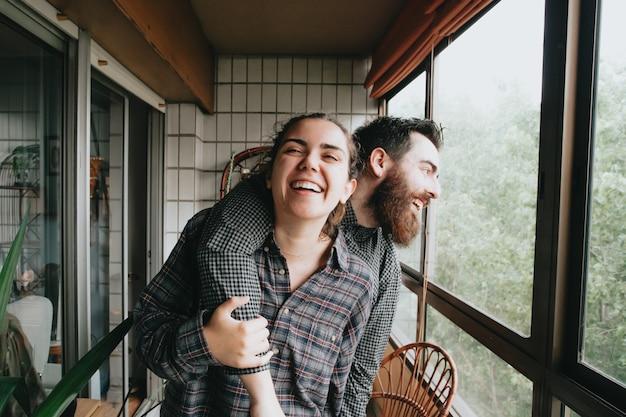 Un couple d'amis riant et s'amusant sur une galerie très lumineuse pendant une journée ensoleillée