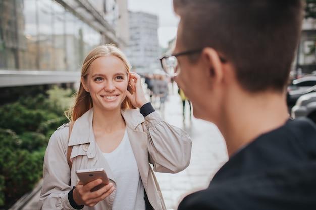 Couple ou amis rire drôles et s'amuser avec un téléphone intelligent dans une grande rue de la ville.