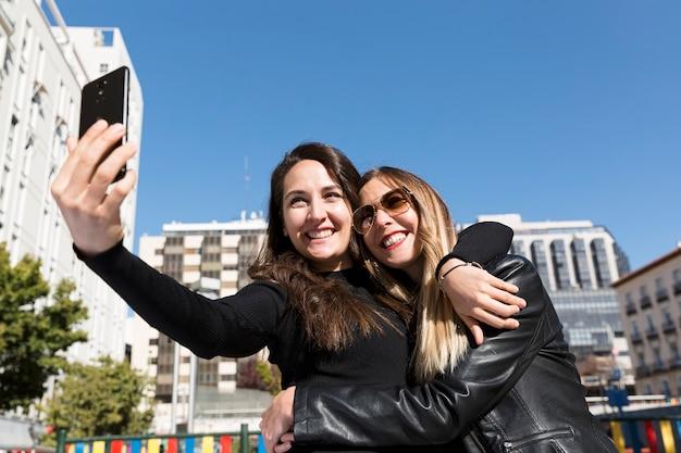 Un couple d'amis souriants ayant un selfie dans la ville.