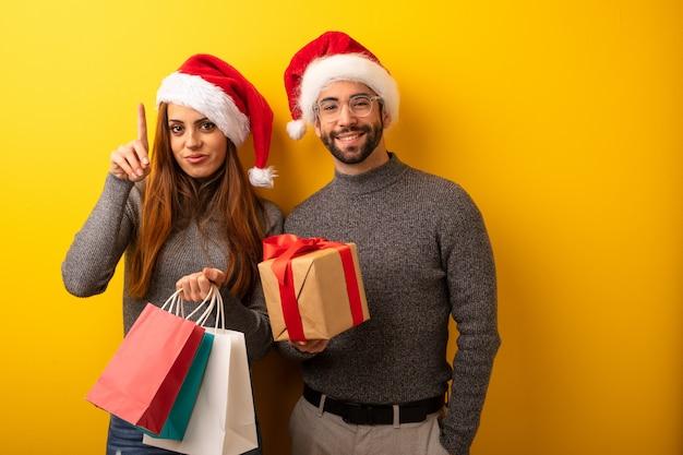 Couple ou amis tenant des cadeaux et des sacs à provisions montrant le numéro un
