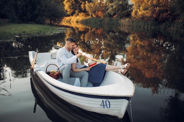 Couple d'amour avec corbeille de fruits allongé dans un bateau sur un lac tranquille au jour d'été. rencontre romantique, balade en bateau, homme et femme marchant le long de la rivière