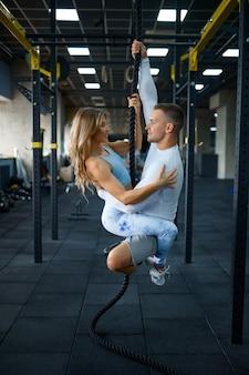 Le couple d'amour est suspendu à une corde, s'entraînant dans une salle de sport