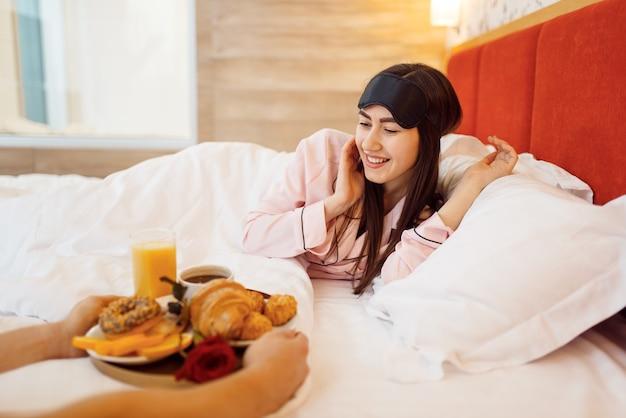 Couple d'amour romantique, petit déjeuner et rose au lit à la maison, bonjour, mari attentionné. relation harmonieuse dans la jeune famille