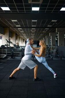 Couple d'amour sportif faisant des exercices d'étirement, entraînement physique en salle de sport