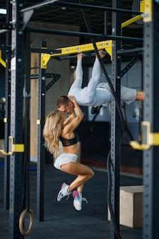 Couple d'amour sportif s'embrassant sur une barre horizontale, s'entraînant en salle de sport