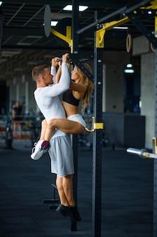 Couple d'amour sportif s'embrasse sur une barre horizontale, s'entraînant en salle de sport