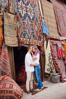 Un couple amoureux achète un tapis et des textiles faits à la main sur un marché oriental en turquie. câlins et visages joyeux et joyeux des hommes et des femmes