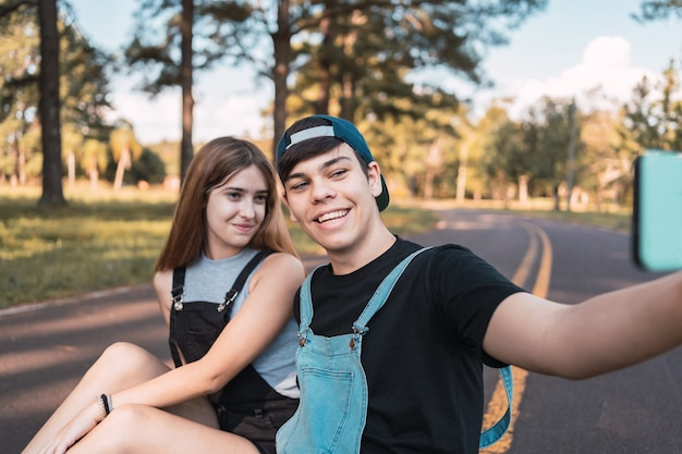 Un couple d'amoureux adolescents prenant un selfie dans un parc