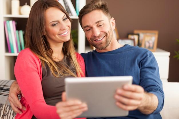 Couple d'amoureux à l'aide de tablette numérique à la maison