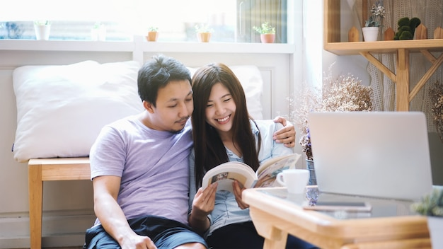 Couple d'amoureux asiatique assis et lisant un livre le matin avec une sensation de chaleur