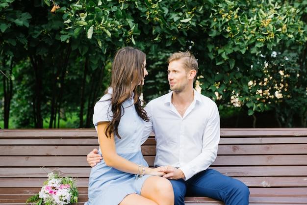 Couple amoureux, asseyez-vous sur un banc dans le parc en été et communiquez.