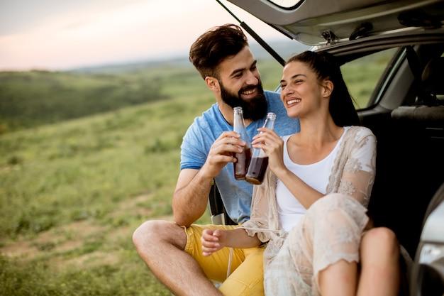 Couple d'amoureux assis dans la voiture trank pendant voyage dans la nature