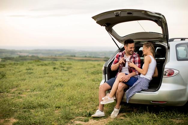 Couple d'amoureux assis dans la voiture trank