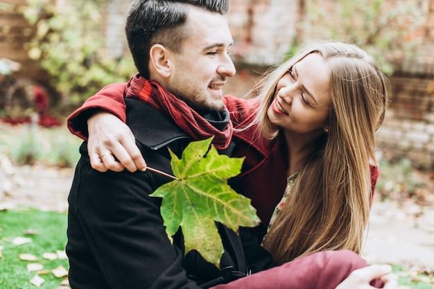 Couple amoureux assis sur les feuilles tombées de l'automne dans un parc et se regardant tout en profitant d'une belle journée d'automne. femme tenant une feuille d'érable