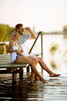 Couple d'amoureux assis sur la jetée sur le lac