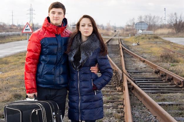 Couple d'amoureux en attente d'un train debout bras dessus bras dessous le long d'une ligne de chemin de fer rural avec leur valise en train de regarder son arrivée