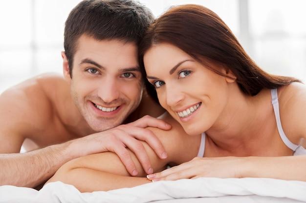 Couple d'amoureux au lit. joyeux jeune couple d'amoureux allongé dans son lit et souriant à la caméra