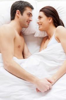 Couple d'amoureux au lit. vue de dessus du beau jeune couple d'amoureux allongé dans son lit et se tenant la main