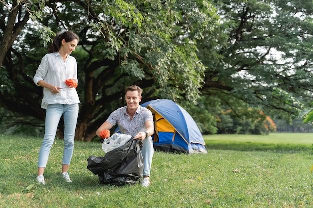 Couple d'amoureux bénévoles portant des gants marchant pour ramasser les ordures dans le parc pour garder l'environnement propre
