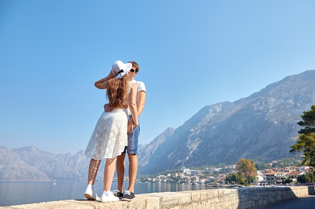 Couple amoureux bisous sur le fond de la côte de la mer, les montagnes et le ciel bleu