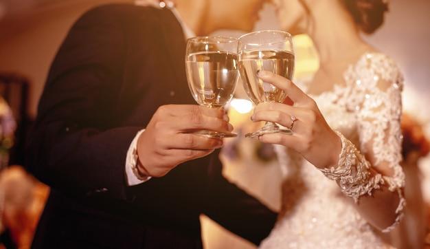 Couple d'amoureux boit joyeusement le jour du mariage. dans la lumière chaude.