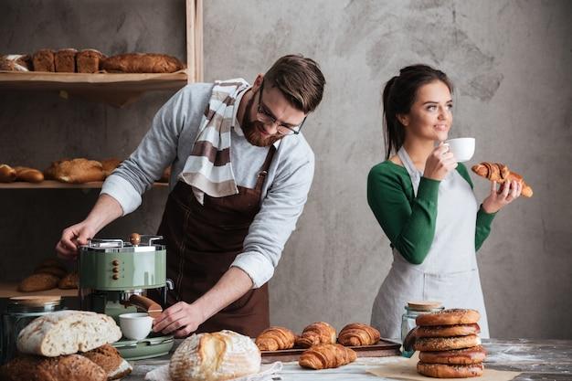 Couple d'amoureux boulangers manger des croissants boire du café