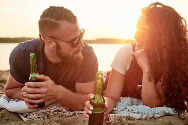 Couple d'amoureux buvant de la bière sur la plage
