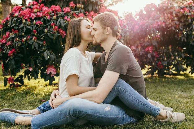 Couple d'amoureux câlins et bisous assis sur l'herbe dans le parc
