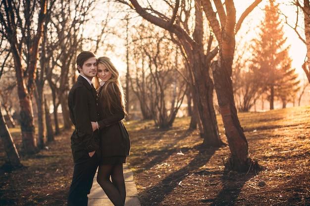 Couple amoureux câlins et bisous au coucher du soleil dans le parc