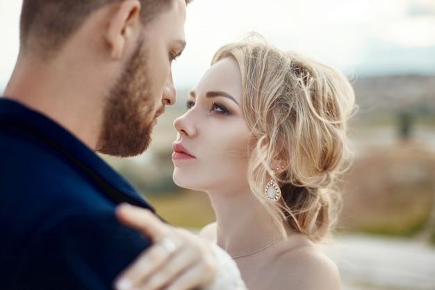 Couple amoureux câlins et bisous dans des montagnes fabuleuses dans la nature. fille en longue robe blanche avec bouquet de fleurs dans ses mains, homme en veste. mariage dans la nature, les relations et l'amour